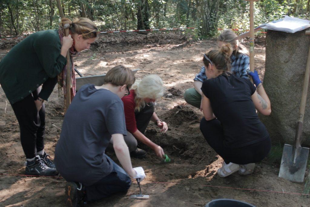 Eine Gruppe Jungarchäologen mit Werkzeugen über einer Grabungsstelle.