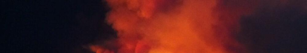 Ein Waldbrand in Kalifornien beleuchtet als helle Pünktchen einen nächtlichen Berghang.