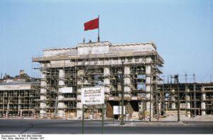 """KF: KFC-46 Film: Exa 22/30 Uhrzeit: 15:31,5 Kamera: Objektiv: Tessar 1:3,5/50mm Filmtyp: Agfacolor-Umkehr-Ultra-T-Film (wie 16/10°DIN); Emuls.-Nr. 4225435, Jan 59 (10.9.57 für 8,45 M gekauft). Anfang Nov 1957 unter Nr.4/277180 von der Kundenfilm-Entwicklungsanstalt des VEB Filmfabrik Agfa Wolfen/Kr. Bitterfeld entwickelt. Am 14.10. abgeschickt, am 16.11.57 zurück (im Werk: 15.10.-13.11.57). Begleitzettel: """"Ihr Film ist teilweise unter- / fast durchweg gut belichtet."""" Einstellung: Ll Blende: 6,3 Zeit: 1 / 50 Entfernung: 15 m Beschreibung: Mit Papa im Bezirk Tiergarten (Ich hatte das Flektogon vergessen).- Brandenburger Tor von SW mit westl. Grenzschild. Gut."""