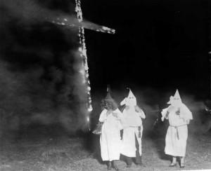 Ku-Klux-Klan-Mitglieder und ein brennendes Kreuz, Denver, Colorado, 1921. Das brennende Kreuz ist wohl das bekannteste Symbol des KKK. Es soll das Licht Jesu Christi symbolisieren.