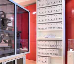 """Der erste Ausdruck der DNA-Sequenz des humanen Genoms (3,4 Milliarden Basenpaare) als eine Reihe von Büchern. Die Nummer auf dem Buchrücken steht für die Nummer des menschlichen autosomalen Chromosoms, dessen Sequenz in diesem Buch enthalten ist. X oder Y auf dem Buchrücken stehen für die menschlichen Geschlechtschromosomen. Ausgestellt werden diese Bücher in dem """"Medicine Now"""" Raum der Wellcome Sammlung in London. Jeder Band ist etwa 1000 Seiten dick und in einer Schrift gedruckt, die so klein ist, dass man sie kaum noch lesen kann."""
