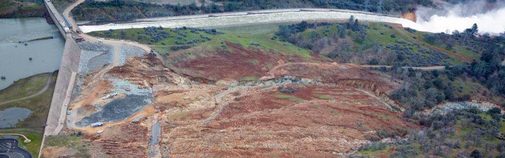 Erosionsschäden am Notauslass des Oroville-Staudamms. Im Hintergrund der beschädigte Hauptüberlauf.