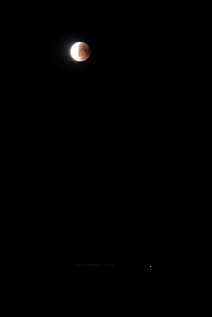 Der Mond hat sich mittlerweile bereits zur Hälfte aus dem Kernschatten heraus- und in den deutlich helleren Halbschatten hineinbewegt. 27.7.2018 23:35 MESZ, Canon EOS6D und Leica Elmarit-R 180, ISO 800, Blende 8, 0.6 Sekunde Belichtungszeit