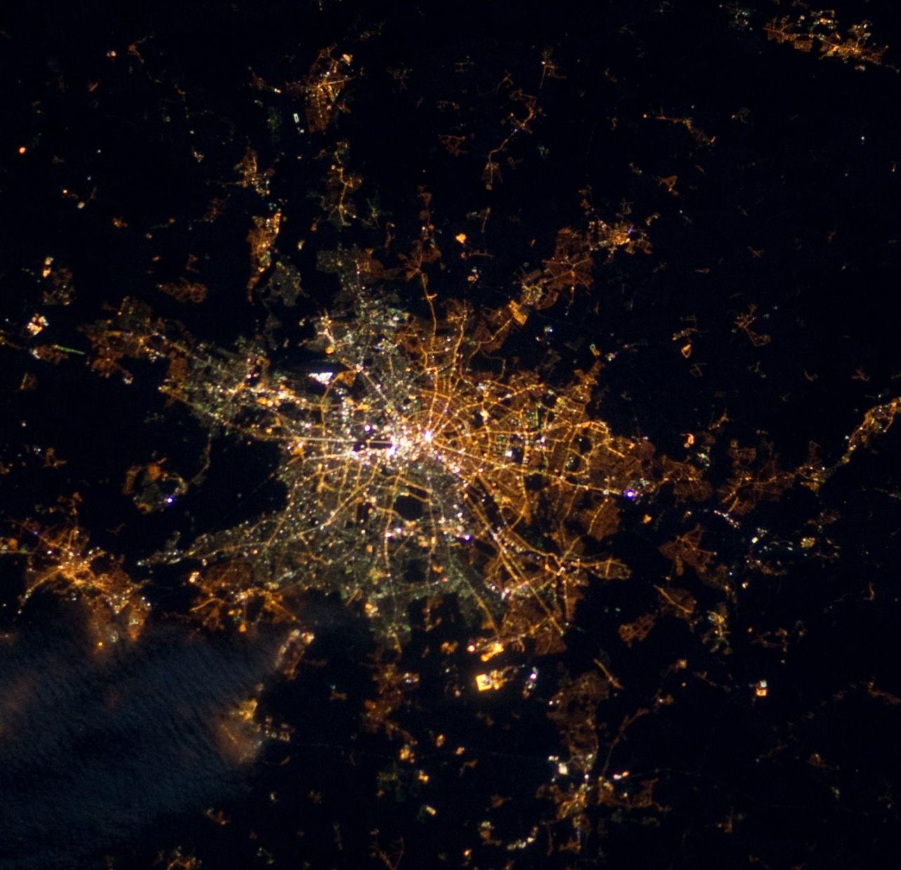 Blick aus der Internationalen Raumstation auf das nächtliche Berlin. Im Jahr 2000 verbrauchte die deutsche Hauptstadt 72.8 Millionen kWh zur Straßenbeleuchtung. Die einstige Teilung der Stadt ist immer noch sichtbar: Im Westen leuchtet immer noch viele alte, weiße Quecksilberhochdrucklampen, im Osten dagegen orangene Natriumdampflampen. Foto: Image Science & Analysis Laboratory, NASA Johnson Space Center.