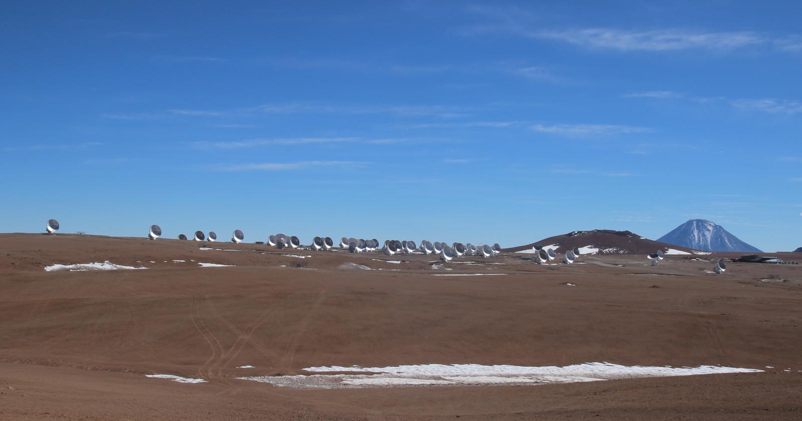 ALMA-Antennen auf dem chilenischen Chajnantor-Hochplateau. Im Hintergrund der 5920 Meter hohe Vulkan Licancabur an der Grenze zu Bolivien.