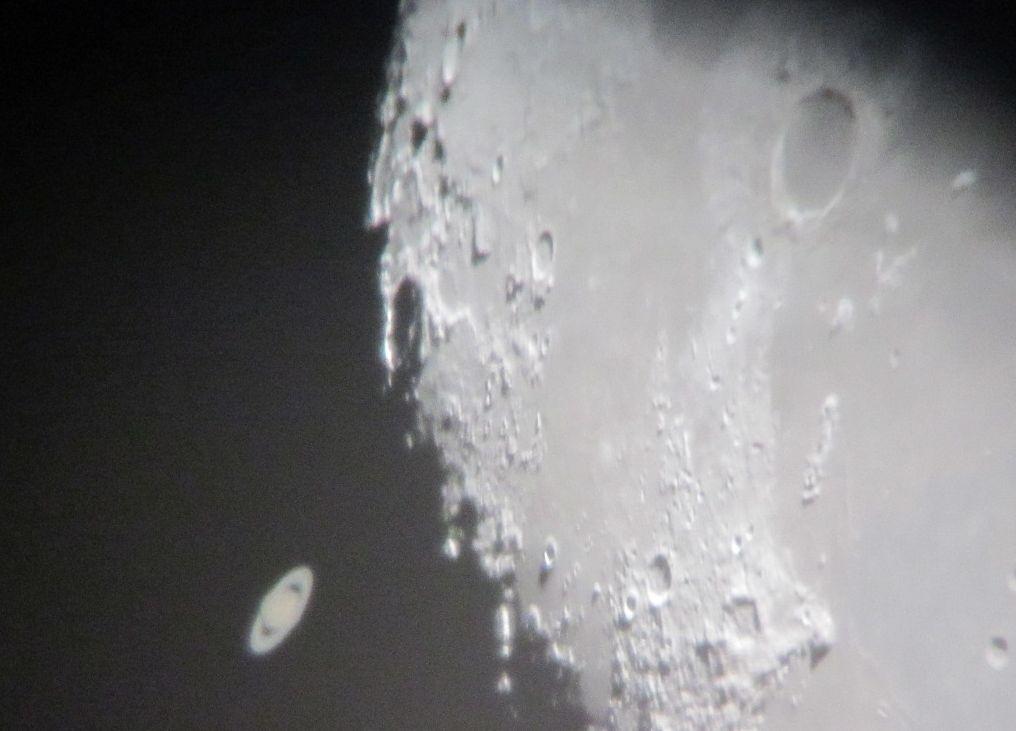 Saturn kurz vor der Bedeckung am dunklen Mondrand. Aufgenommen mit einer Canon Powershot A1200, freihand ans Okular gehalten.