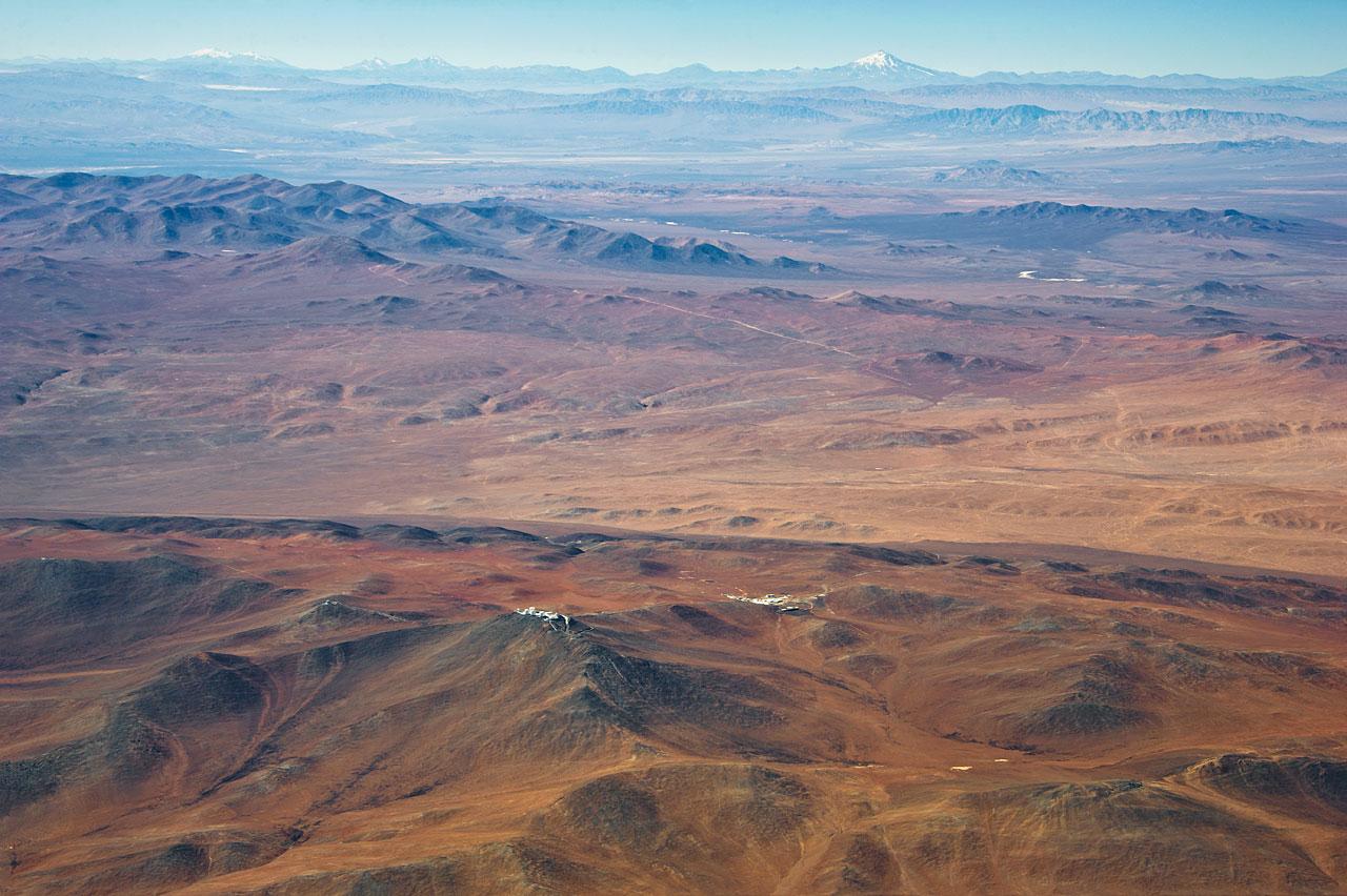 Der Cerro Armazones (links oberhalb der Bildmitte) hinter den Kuppelbauten der vier großen 8,2-Meter-Hauptteleskope des Very Large Telescope auf dem Cerro Paranal. Am Horizont ist der schneebedeckte 6720 Meter hohen Vulkan Llullaillaco zu erkennen, der sich ganze 190 km östlich an der Grenze zu Argentinien befindet. (Bild: ESO/M. Tarenghi)