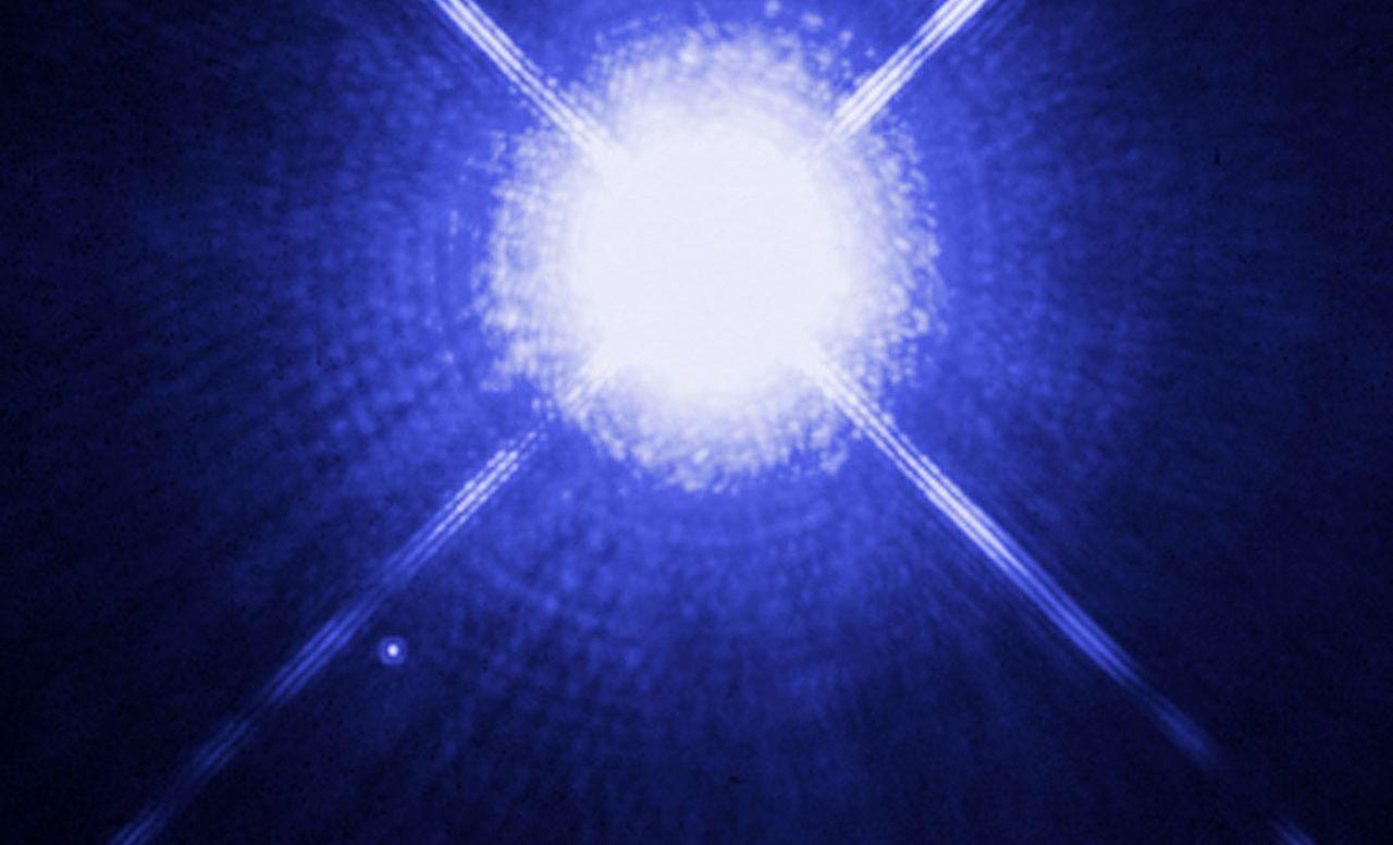 Sirius A (mitte) und Sirius B (links darunter) mit dem Hubbleteleskop gesehen. Dass man den Weißen Zwerg Sirius B überhaupt mit einem ganz normalen Amateurfernrohr sehen kann, mag unglaublich erscheinen - aber es geht (Bild: NASA, ESA, H. Bond (STScI), and M. Barstow (University of Leicester)