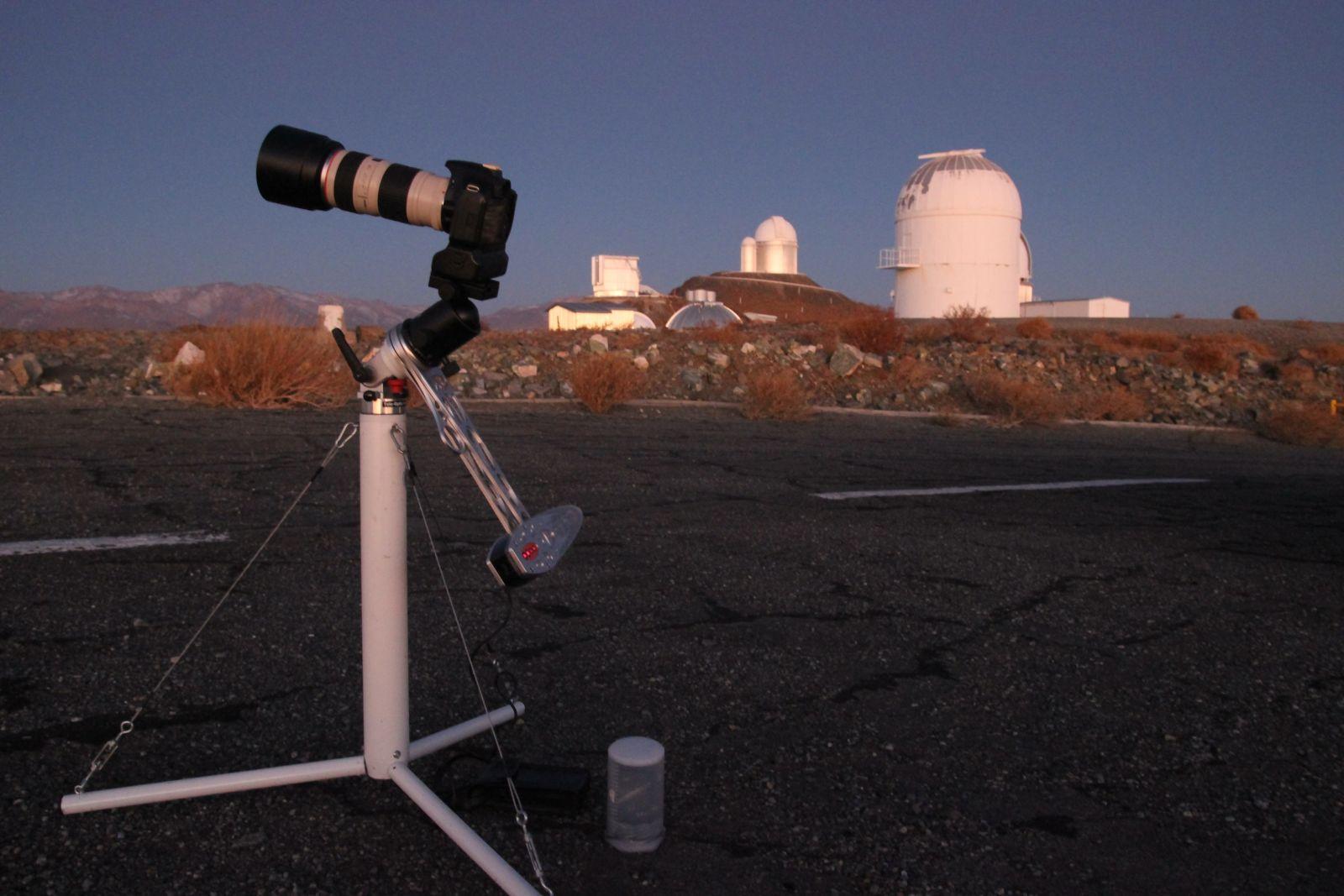 Kamera und Zubehör, bereit für die Nacht. Im Hintergrund einige Kuppeln des La-Silla-Observatoriums.