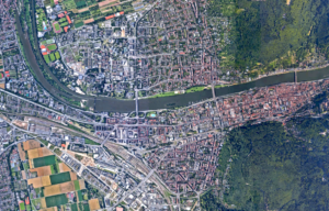A satellite image of Heidelberg, showing three bridges all crossing a river that runs horizontally across the map