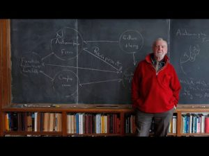 Robert Langlands, standing by a blackboard with mathematics on