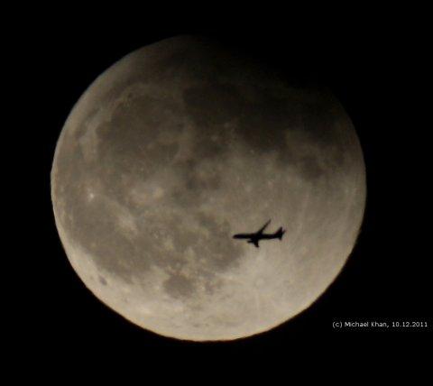 Mond gegen Ende der totalen Mondfinsternis am 10.12.2011 mit kreuzendem Verkehrsflugzeug, aufgenommen aus Darmstadt-Eberstadt, Quelle: Michael Khan