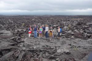 Kurze Sammelpause auf Pahoehoe-Lava, bevor es auf den A'a-Brocken weitergeht: Die Crew mit Geologe (vierter von links) und Reporterin (rechts außen).