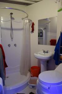 Das Bad im Erdgeschoss: Dusche, Waschbecken und Komposttoilette. Den Eimer nutzen wir, um einen Teil des Duschwassers aufzufangen und wiederzuverwenden.