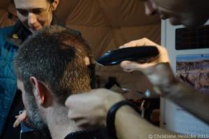 Andrzej lässt sich eine Haarprobe nehmen. Ich habe auch so einen kahlen Fleck, aber meiner wird von den darüber liegenden Haaren verdeckt.