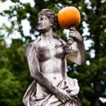 Halbnackte Statue mit festen, steinernen Brüsten und Kürbis.