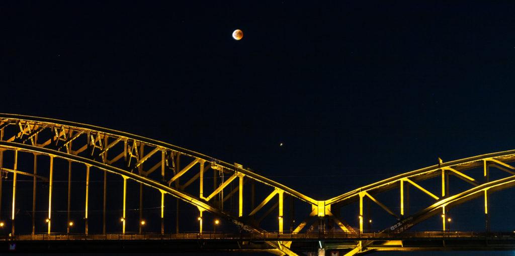 Mondfinsternis in Köln über einer Eisenbahnbrücke