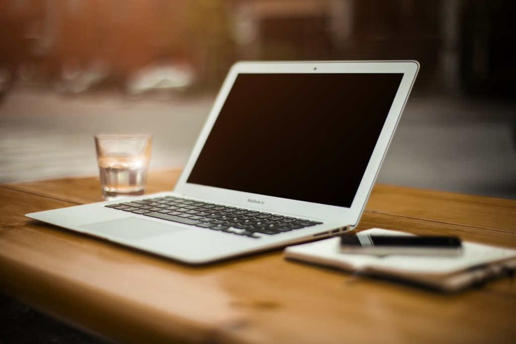 Ein Arbeitsplatz aus Laptop, Notizbuch mit Stift und einem Glas Wasser