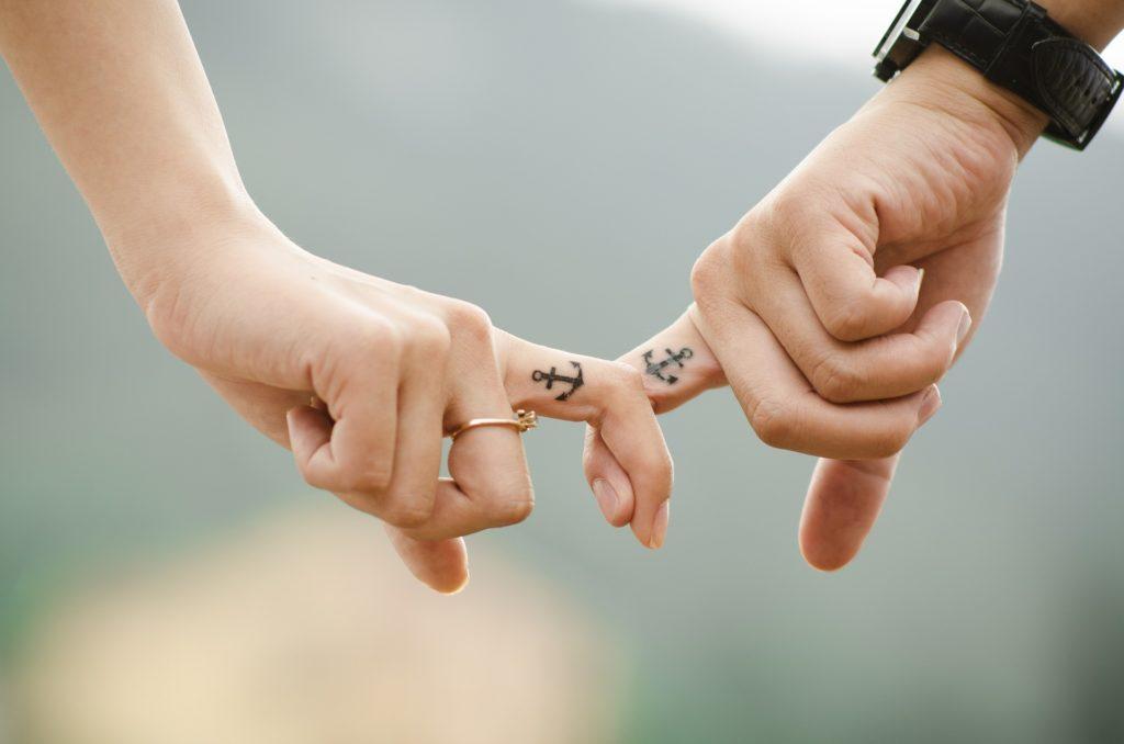 Zwei Hände, die sich an den Zeigefingern festhalten