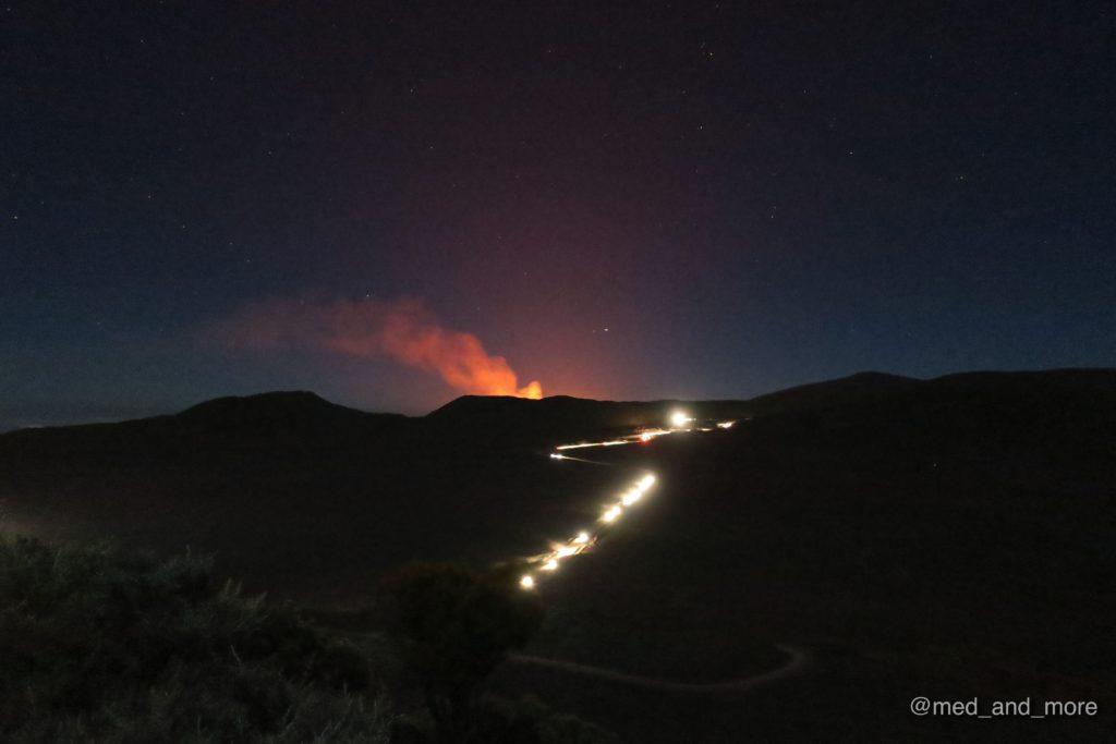 Am Pas de Sables vermischen sich die Lichter der Autoschlangen mit den Wolken der glühenden Lava.