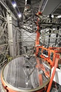 """Blick vom sechsten Stock auf den linken oder blauen """"Arm"""" des LBT. Ganz oben sieht man den Sekundärspiegel, der bei der gregorianischen Montierung über dem Primärfokus liegt. Links darunter ist die die Kamera LBC blue zu erkennen. Wenn sie verwendet wird, wir der Sekundärspiegel aus dem Strahlengang geschwenkt und LBC wird eingeschwenkt."""