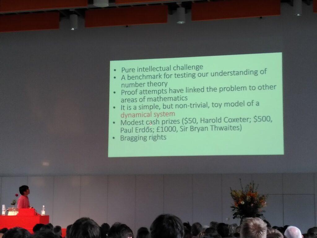 Eine Folie des Vortrags von Terry Tao über die Collatz Vermutung, wo verschiedene Punkte aufgelistet sind. Namentlich: a) Intellektuelle Herausforderung, b) ein Test für die Zahlentheorie, c) Beweis könnte für andere Probleme hilfreich sein, d) simples Modell eines dynamischen Systems. e) überschaulicher Preis von 1000 Pfund. f) Angeber-Rechte.