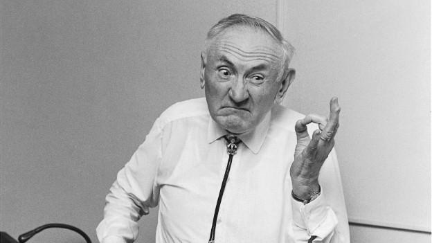 Fritz Zwicky zeigt mit Körpersprache non-verbale Kommunikation