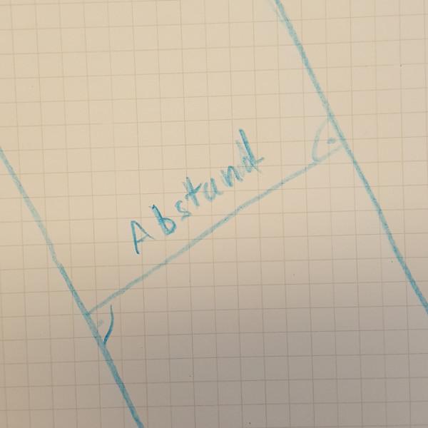 Zwei parallele Geraden laufen durch das Bild. Der Abstand ist durch eine Linie eingezeichnet.