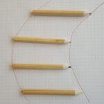 Vier Buntstifte. Ihre Spitzen und ihre Enden sind je durch eine Kurve verbunden.