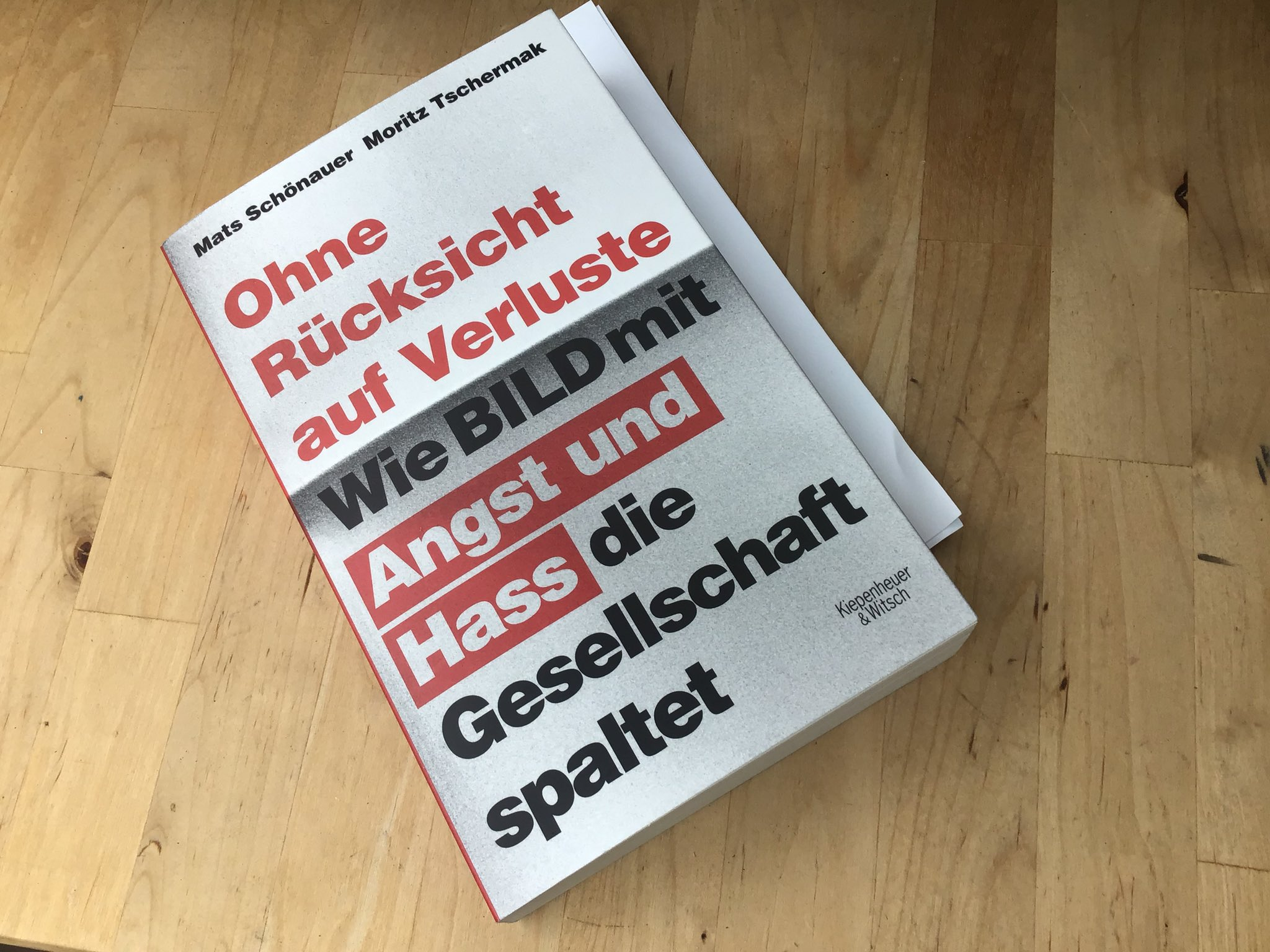 """Buch auf Holztisch: """"Ohne Rücksicht auf Verluste – wie BILD mit Angst und Hass die Gesellschaft spaltet"""""""