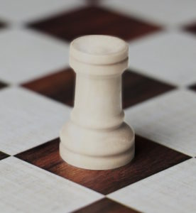 Wissenschaft im Elfenbeinturm oder ein Problem der Sichtbarkeit? Symbolbild: Elfenbeinfarbener Turm auf einem Schachbrett