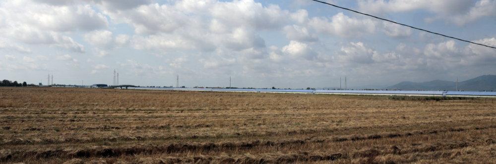 Gravitationswellendetektor Virgo aus der Ferne: eine blaue Röhre in der Landschaft