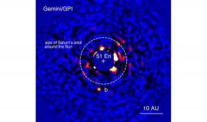 Nahinfrarot Bild des Exoplaneten 51 Eri b. Der Zentralstern wurde bei der Beobachtungen mit einem Coronagraphen abgedeckt, um den leuchtschwächeren Planeten sichtbar zu machen. In dem Bild wurde das verbleibende Sternenlicht zusätzlich herausgerechnet und die ursprüngliche Position des Stern ist mit einem Kreuz angedeutet.