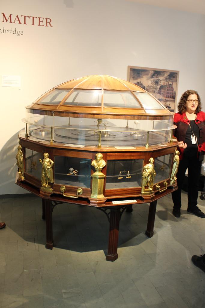 """""""GRand Orrery"""", eine mechanisches, d.h. quasi uhrwerkbetriebenes Planetarium mit Ben Franklin, Isaac Newton und dem damaligen Gouverneur von Massechussetts als Seitedekoration. Obwohl während der zehnjährigen Bauzeit der Planet Uranus entdeckt wurde, wie Kuratorin Sara Schechner erläutert, wurde dieser nicht ins Modell einbezogen."""