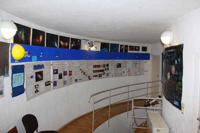 Poster zu verschiedenen Themen der Astrophysik und eine ungefähre Entfernungsskala der Planeten des Sonnensystems schmücken die Wand dort, wo die Treppe die Planetariumsetage erreicht.